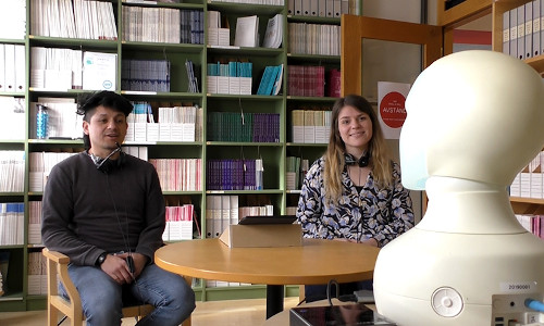 Researchers demonstrate the experimental setup they used to observe how group participants are prompted to speak up in an activity led by a robot.